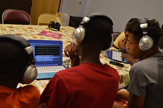 Three young African American boys working at laptops while wearing headphones.