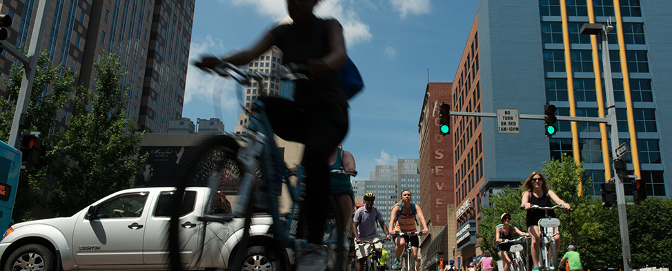 People riding bikes through Downtown Pittsburgh during 2016 OpenStreetsPGH when certain streets were closed to automobiles.