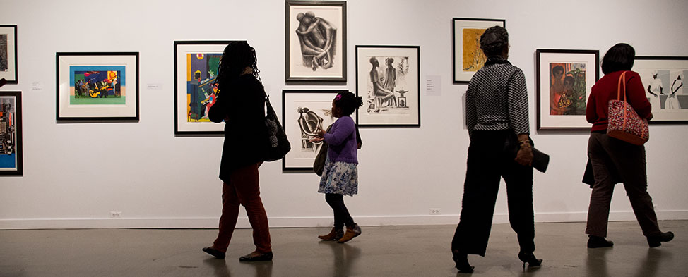 A mother and her daughter examine the exhibit of African American art at the August Wilson center, and two other women walk by in the opposite direction.