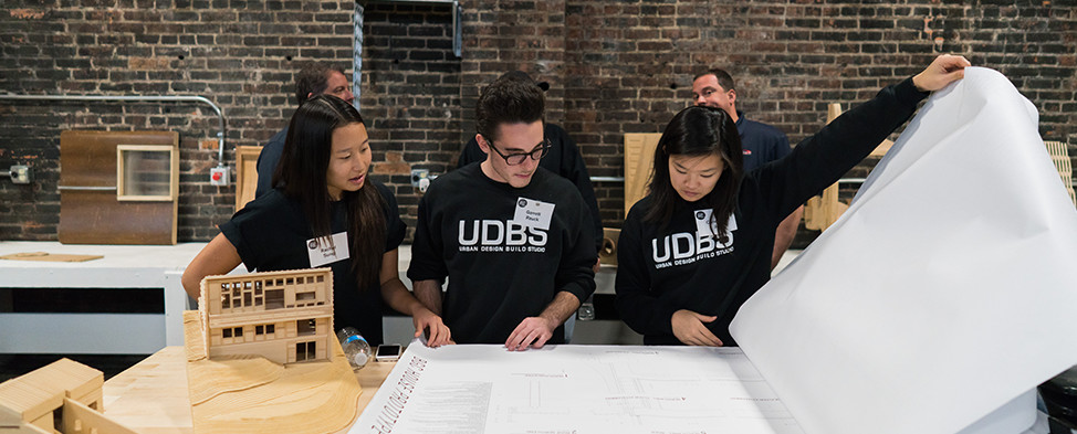 Three students from the Urban Design Build Studio are shown looking through blueprints during the Project RE dedication at Construction Junction.