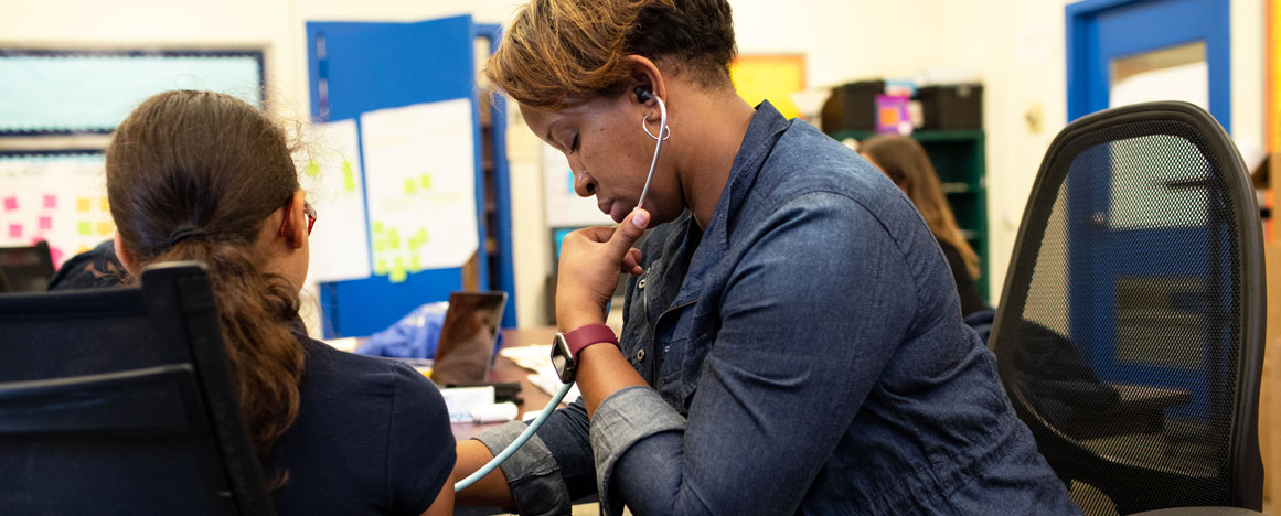 A woman with a stethoscope is tending to a young girl in an asthma clinic in Hazelwood