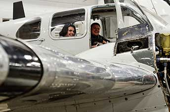 Two students sitting inside a plane at the Pittsburgh Institute of Aeronautics.