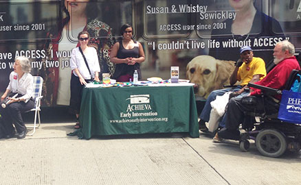 Photo taken during the 3 Rivers Arts Festival celebrating the 25th anniversary of the Americans with Disabilities Act. Image shows several people in wheel chairs around an informational table provided by Achieva.