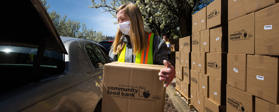 Female volunteer wearing face mask and gloves loading a box of food from the Greater Pittsburgh Community Food Bank drive-through food distribution on April 6.