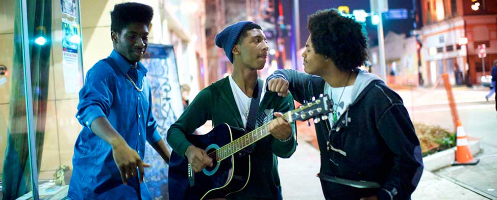 Three young African America men are singing on a city street. One is playing the guitar.