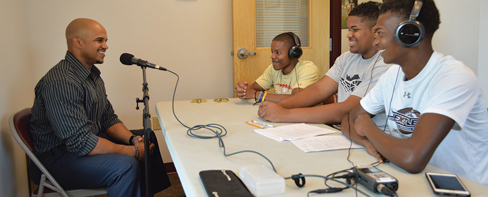 Three young black men wearing headphones interviewing a black man, who is speaking into a microphone.