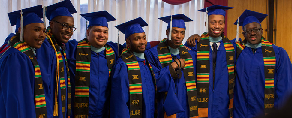 Heinz Fellows standing arm-in-arm in their graduation attire at their Duquesne University graduation.