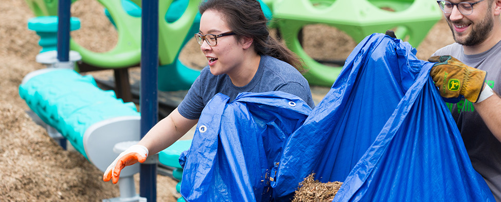 Two volunteers carrying mulch in a blue tarp on Build Day at the Hazelwood KaBOOM! playground.