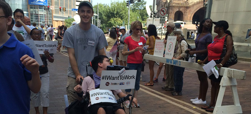 "Street view during Labor Day Parade in Pittsburgh showing young man pushing another in a wheelchair who is holding a sign that says, ""#IWantToWork."