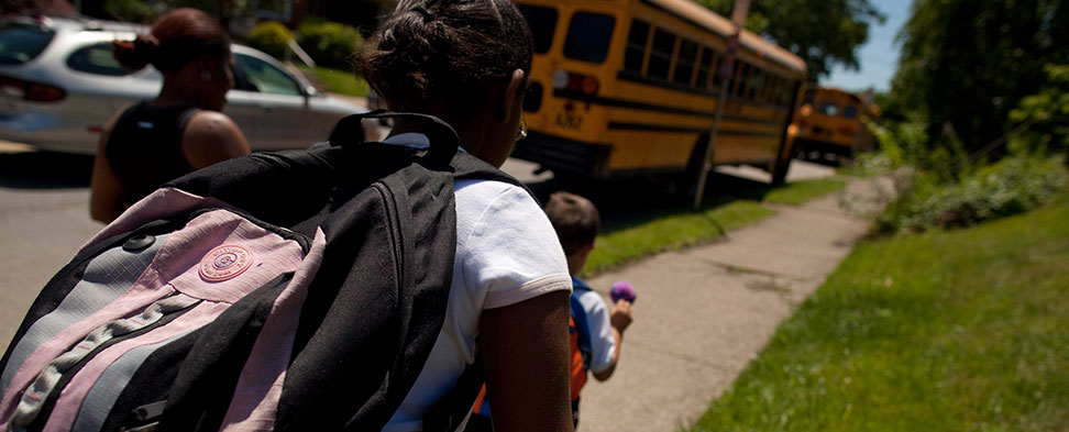 Photo taken from behind of children boarding their school bus to attend the Environmental Charter School.