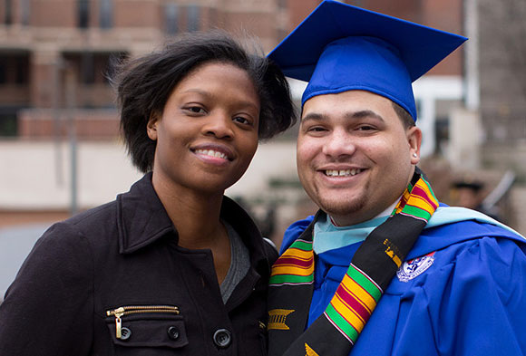 Heinz Fellow, Matthew Tansey, and a guest smiling at his Duquesne University graduation.