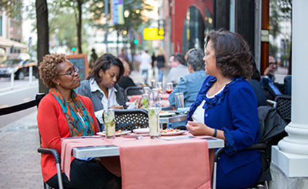 Three women having lunch on a sunny day at the outside tables on Penn Avenue
