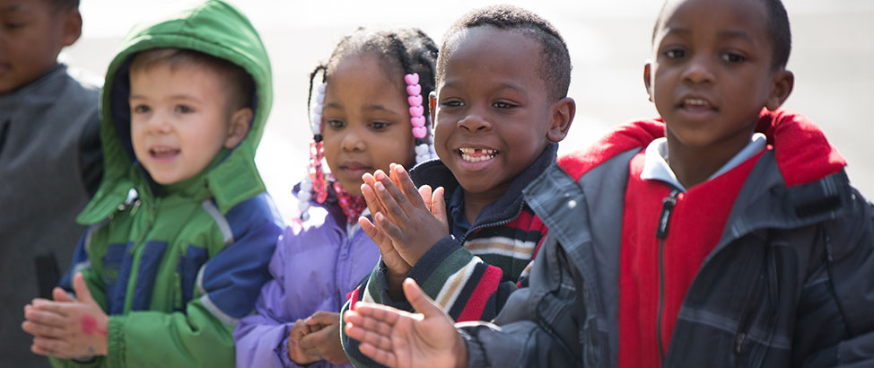 Four happy young children clapping their hands and smiling when the Storymobile visited Propel Elementary school in Hazelwood.