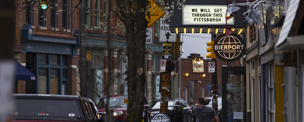 "photo of man walking down street under marquee which says, ""We will get through this Pittsburgh."""