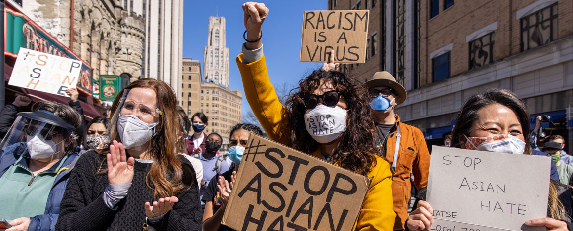 "Sandra Oh wearing a mask and holding a sign that say, ""#Stop Asian Hate"" in a crowd of protestors"