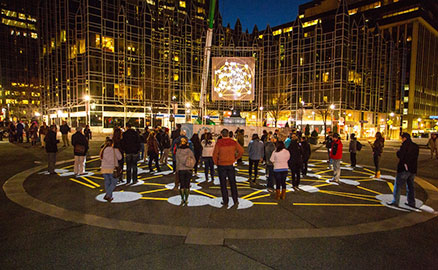 "Nighttime image of a group of people interacting with the ""Congregation"" public art project in Market Square in Downtown Pittsburgh. This work was created by KMA and presented by Market Square Public Art."