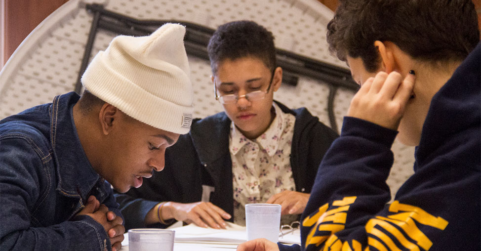 Three young black men, participants in the Dreams of Hope program, are working together around a table.