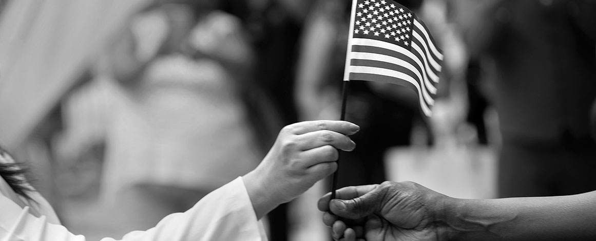Two hands meet as one person hands off a small American flag to the other.