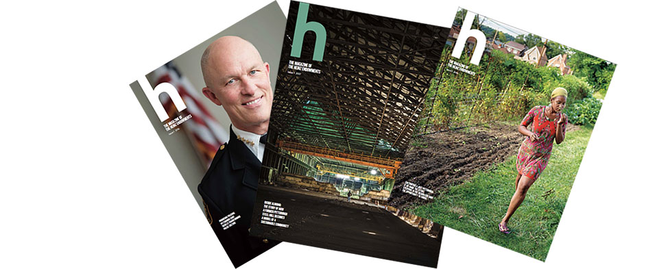 Covers of three issues of h magazine, fanned-out.