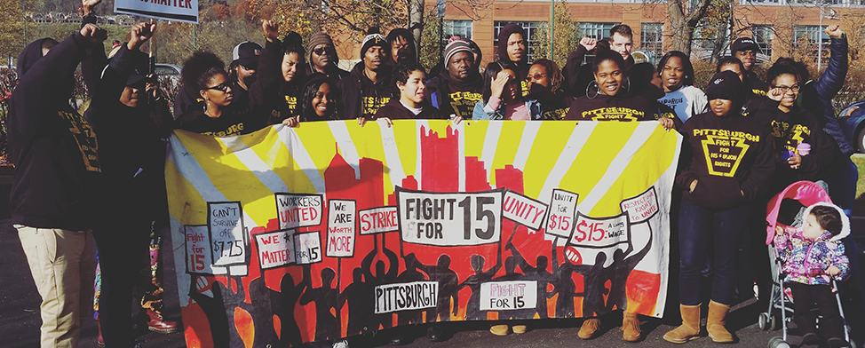 "Large group of workers posed holding a ""Fight for 15"" banner"