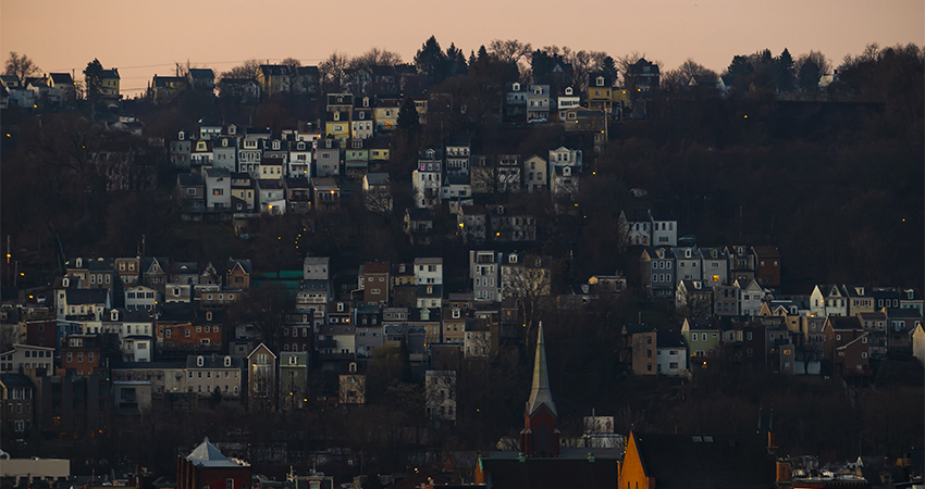 houses on a hillside with a pink sky above