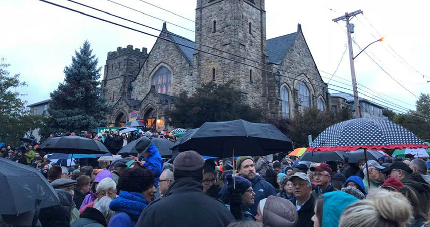 Large crowd of people who gathered in the rain for the Saturday night vigil at the corner of Forbes and Murray in response to the Tree of Life shooting