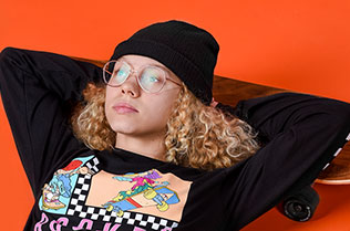 Young girl with blonde hair and glasses, wearing a black hat and T-shirt is resting on her back with her hands behind her head and on a skateboard
