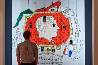 "Man standing in front of ""Miss Dior's shopfront"" examining the image."