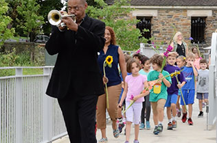 Frick Environmental Center during 2016 opening celebration. Man in the front is playing the trumpet and a long line of children are following him.