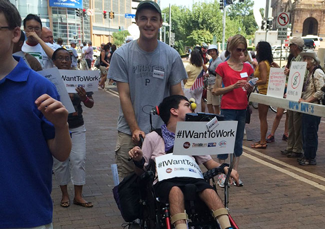 Street view during Labor Day Parade in Pittsburgh showing young man pushing another in a wheelchair who is holding a sign that says, #IWantToWork.