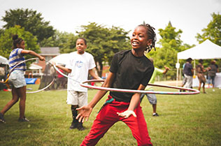 Three African American youth in park playing with hula hoops