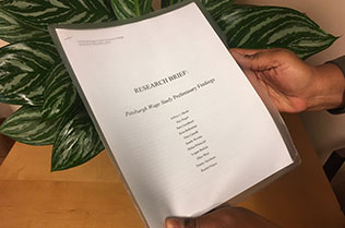 Image of hands holding a copy of the preliminary report.