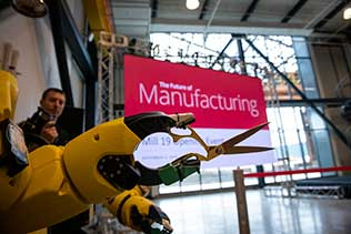 "Robotic arm is holding a pair of scissors. Operator is sitting behind the arm and there is a banner in the background that says, ""The Future of Manufacturing"""